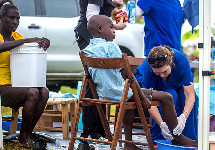 Young Haitian boy receives treatment as mother waites with Disaster Relief Bucket.