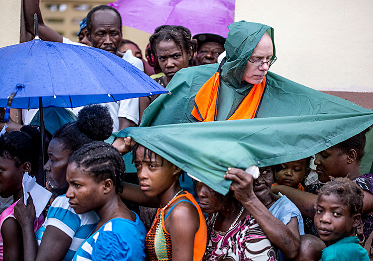 Volunteer covering Haitians from the rain.