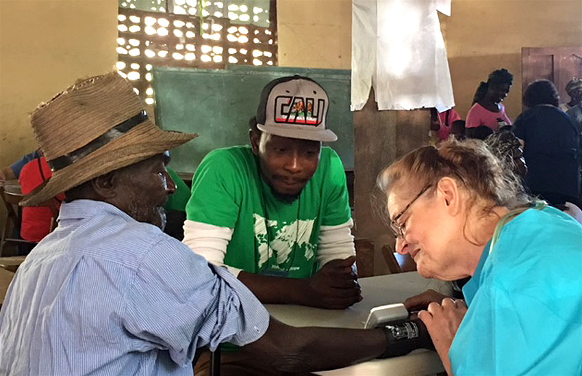 Dieuferly translates for the elderly man and the nurse during our Mobile Medical Clinic.