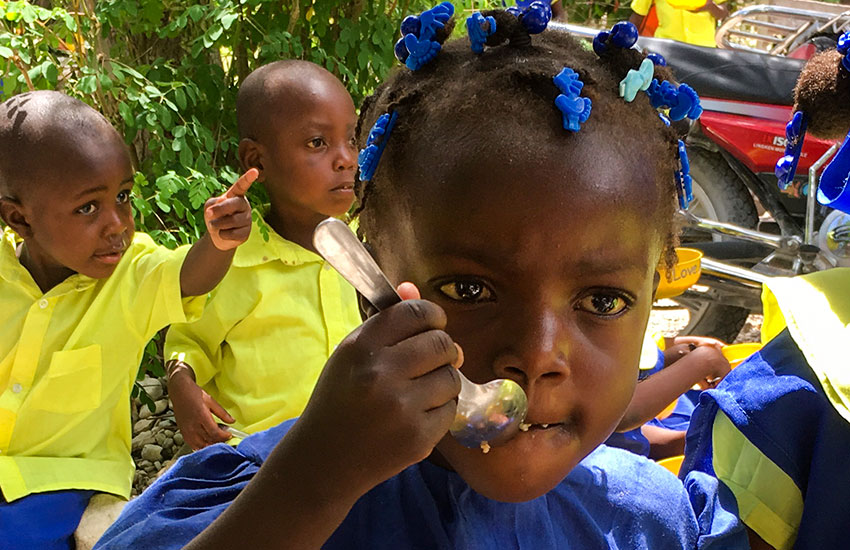 Schoolchildren eating at the Love A Child Lastik School.