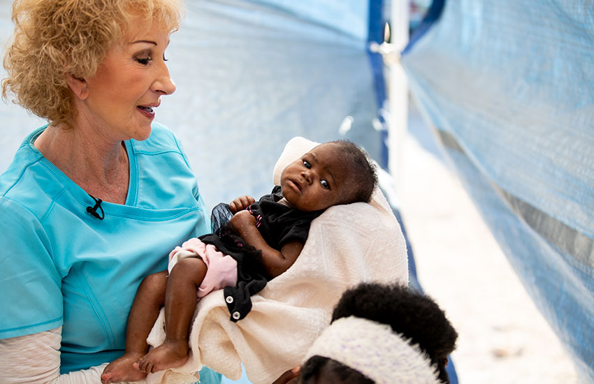 Sherry holds a young child suffering from Kwashiorkor malnutrition.