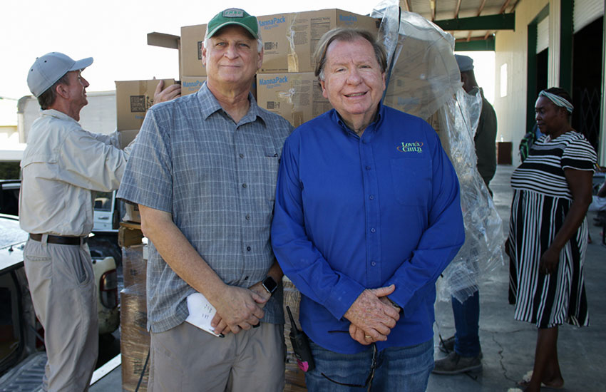 Mark Crea from Feed My Starving Children and Bobby watch the monthly food distribution.