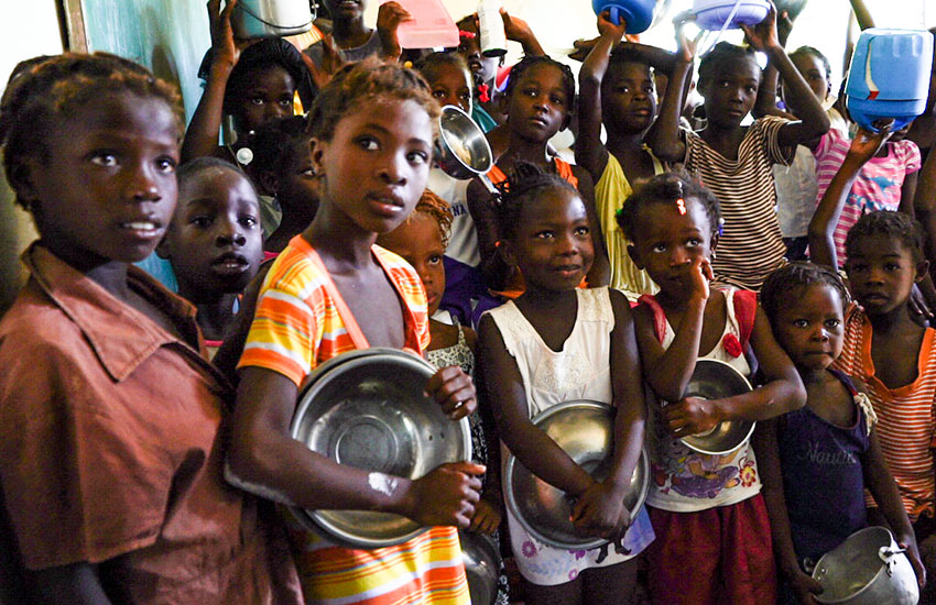 Hungry children wait to receive a bowl of hot, nourishing food.